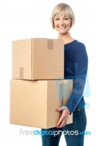beautiful-woman-carrying-cardboard-boxes-100218620